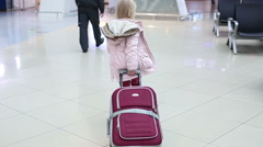 Small blonde girl in winter coat with suitcase walking across waiting hall. Stock Footage