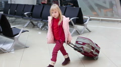 Small blonde girl in winter coat with suitcase waiting across waiting hall in th Stock Footage