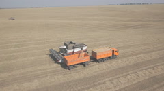 Process of unloading combine hopper into back of a truck on field - stock footage