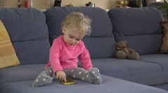 Babysitter help cute baby girl to use smart phone sitting on sofa - stock footage