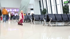 Small blonde girl in winter coat with suitcase waiting an airplane. Airport. Stock Footage