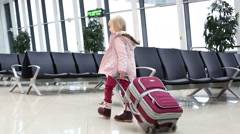 Small blonde girl in winter coat with suitcase walking across hall in an airport Stock Footage