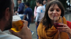 Young couple drinking wine and beer in cafe in the city, super slow motion Stock Footage