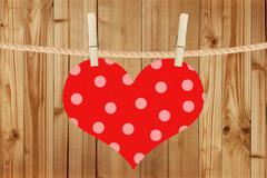 red heart hang on clothespins over wooden background - stock photo