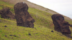 Moai Statues half burried on the hillside of a mountain on Easter Island Stock Footage