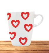White cup with red hearts on wooden table isolated on white - stock photo