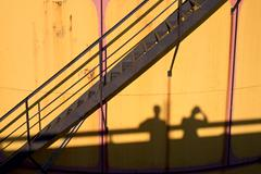 People shadows on old metal tanks in power plant, - stock photo