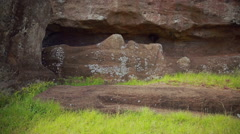 Close-up shot of the  Moai statue carved out from the rock but still in there Stock Footage
