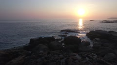 Perfect sunset reveal Aerial Shot young couple standing on Rocks Romantic scene Stock Footage