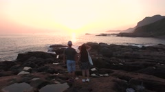 Young Adventurous couple walking together on Rocks at Sunrise Aerial Shot. Stock Footage