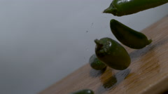 Lots of green hot peppers falling in slow motion onto cutting board, moving shot Stock Footage