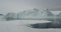 Scenic pan of iceberg in calm seas in arctic evening Stock Footage