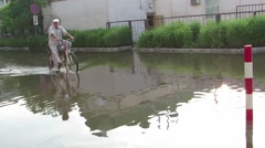 Man on a bicycle goes on water Stock Footage