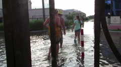 People in bathing suits go through water on the street Stock Footage