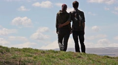couples goes to each other, then hug, then look on mount, turn around and walk - stock footage
