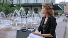 Young woman with suitcase on plaza with jet fountains at front of the train stat Stock Footage