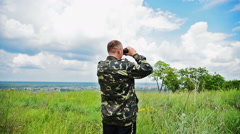 Back side man looks in the binocular at the nature Stock Footage