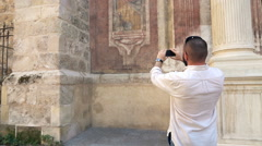 Young man taking photo with cellphone of fresco designed the facade of the churc Stock Footage