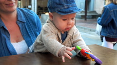 Cute, funny small baby playing with toy sitting on the mother's knees in cafe, s Stock Footage