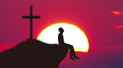 The man sit near the cross against the background of sunrise. Real time capture Stock Footage