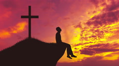 The man sit near the cross against the background of sunrise. Real time capture - stock footage