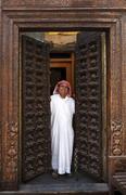 Smiling man opening ornate doors Stock Photos