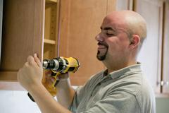 Contractor using power drill in house Stock Photos