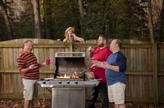 Woman watching neighbors barbecuing food Stock Photos