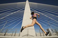 Low angle view of Caucasian woman jogging on urban bridge Kuvituskuvat