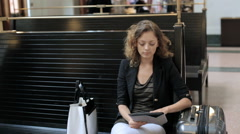 Young woman with suitcase waiting for her train inside of the train station. Stock Footage
