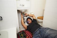 Mixed race man fixing sink plumbing Stock Photos
