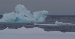 Large blue iceberg drifting past ice edge Stock Footage