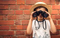 Boy in a straw hat looks in binoculars - stock photo