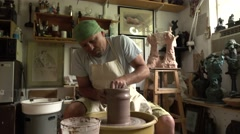 The artist works with clay at art studio and creates a pitcher Stock Footage