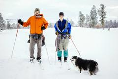 Caucasian couple and dog cross-country skiing in snowy field Stock Photos