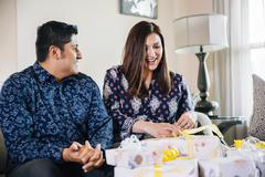 Hispanic couple opening gifts at baby shower Stock Photos