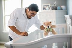 Hispanic father waving toy for baby in nursery Stock Photos