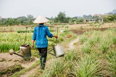 Farmer carrying water in rural crop field Stock Photos
