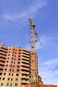 Crane and building construction site against blue sky - stock photo