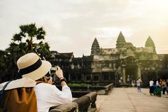 Caucasian tourist photographing Angkor Wat ruins, Siem Reap, Cambodia Stock Photos