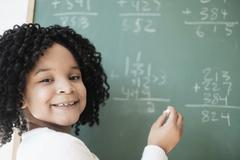 African American student writing on chalkboard in classroom Stock Photos