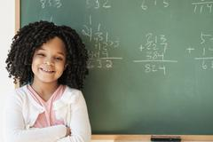 African American student smiling near chalkboard in classroom Stock Photos