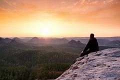 Adult in black trousers, jacket sit on cliff's edge Stock Photos