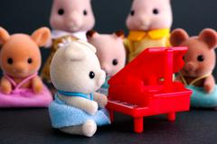 Sylvanian family Pig Baby sits by red piano in front of audience. - stock photo
