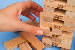 Human hand removing one block from Jenga tower Stock Photos
