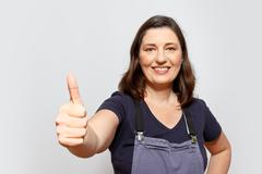 woman dungarees thumbs up sign - stock photo
