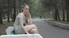 Thoughtful young woman sitting on a bench - stock footage