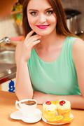 Woman with coffee and cake in kitchen. Gluttony. - stock photo