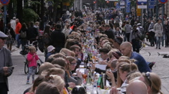A lot of people eating and drinking at the same table on the street. Time Lapse. - stock footage