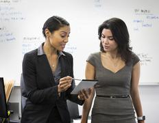 Businesswomen talking with notepad in office Stock Photos
